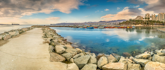 Panoramic view on stone walking pier and marine lagoon from central walking promenade in Eilat - famous resort city in Israel