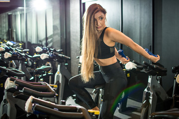 Sporty fitness young woman with dumbbells working out on exercise bike at gym.