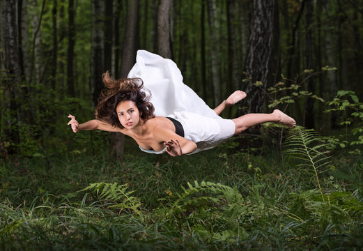 Zero gravity. Young beautiful woman flying in a dream in a summer forest. White dress and hair in the air
