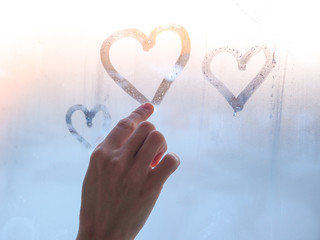 A beautiful female hand draws a heart on a misty window.