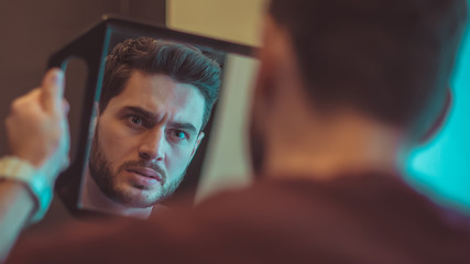 Unhappy with his appearance. A man looks in the mirror.