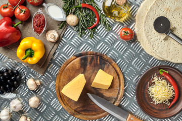 Cheese, different vegetables on metal table. Ingredients for traditional italian pizza.