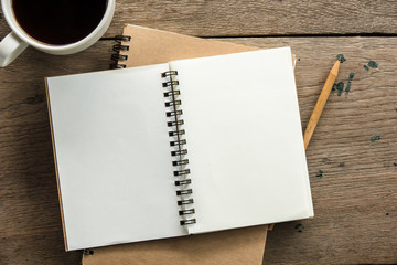 Top view of blank notebook with white coffee and natural light on wooden table.