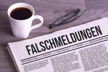 Eine Lesebrille, Tasse Kaffee und eine Zeitung mit Falschmeldungen