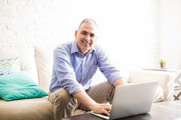 Happy mature man using on laptop in living room