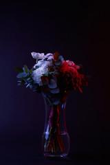 bouquet of different flowers in vase on dark
