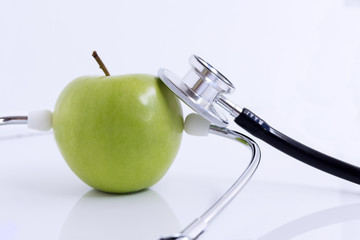 Stethoscope and green apple isolated on white table background.