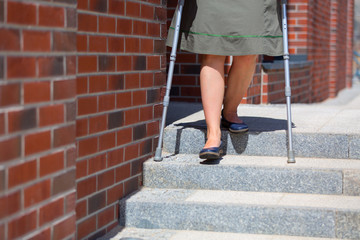 woman going down the stairs using crutches