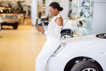 Professional african female salesperson working in car dealership