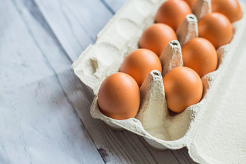 Chicken eggs in cardboard container on wooden table,