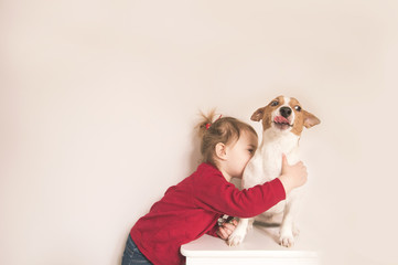 Child girl and jack russell dog have fun at home