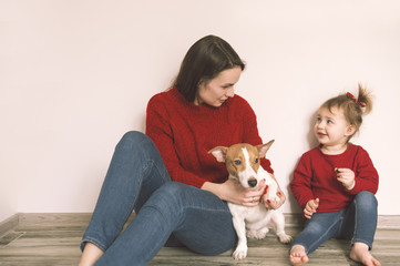 Mom with child and pet dog have a fun at home
