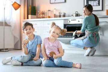 Little kids eating cookies near oven in kitchen while their mother cooking on background