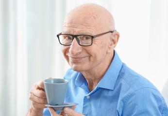 Senior man with hearing aid drinking tea indoors