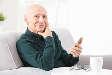 Senior man with hearing aid using smartphone indoors