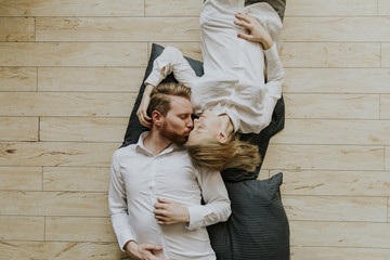 Loving couple lying and kissing on the floor