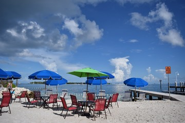Seaside beach with tables and umbrellas on sunny day with blue sky