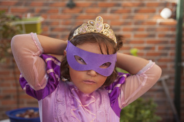 Girl in a purple princess costume, eye mask and crown dressing up. Outdoors.