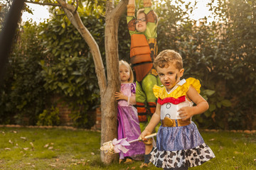 Kids with costumes playing in the garden. Outdoors.
