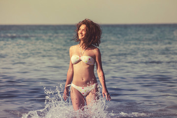 Beautiful young woman with long hair runs along sea beach, splashes of water. Happiness, joy, vacation and travel concept