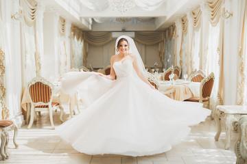 Beautiful bride posing in wedding dress in fashion hotel