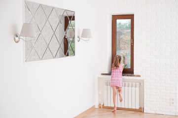 thin little girl looks out the window in bright new house