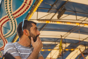 Side face man smoking looking around in a funfair in village