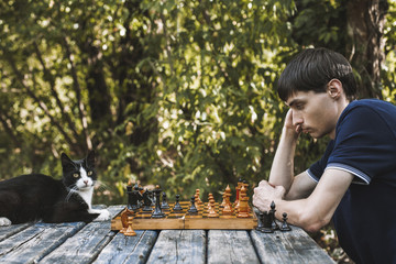 Side view of serious man looking at chess pieces by cat on wooden table at backyard