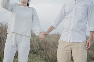 Couple man and woman holding hands to show love and warmth. Dry grass in the field vintage style.