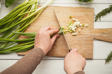 Woman cutting spring onion for salad