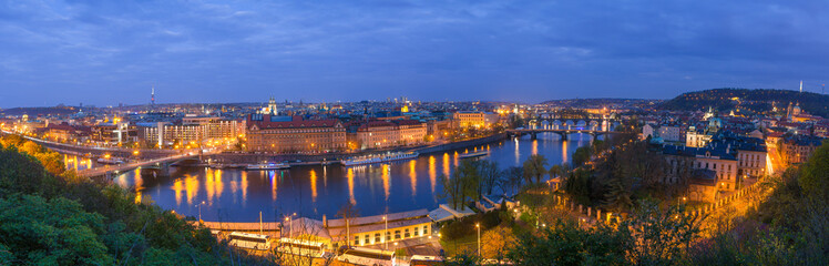 Old town and bridges over Vltava river illuminated night panoramic view from Letenske garden....