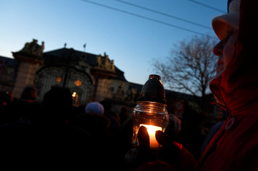 Participant brings candle for a march in honor of murdered Slovak investigative reporter Jan Kuciak  in Bratislava