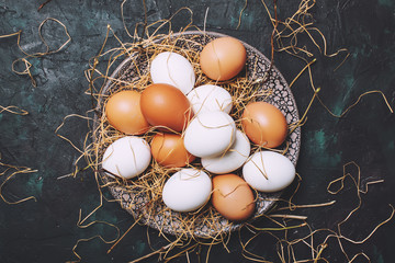 Multicolored chicken eggs with straw and branches, spring Easter composition, black background, top view