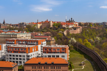 Prague skyline with wall, castle and living blocks red rooftops with park and trees