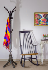 Interior shot of vintage rocking chair, coat hanger and flower pot on old style vintage table on background of off white wall with one hanged painting including clipping path for painting
