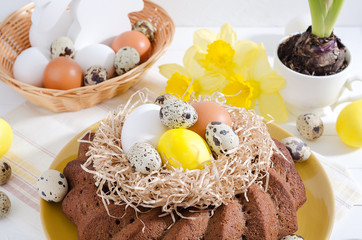 Easter still life, Easter cake with dyed eggs in a nest, daffodils and hyacinth in a cup on a white rustic wooden background