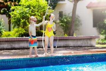 Kids play with water hose at swimming pool.