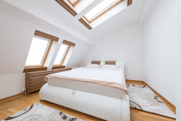 Bedroom interior in luxury loft, attic, apartment with roof windows