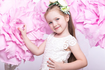 Little fairy girl in white dress on a background of flowers. Photo taken in studio