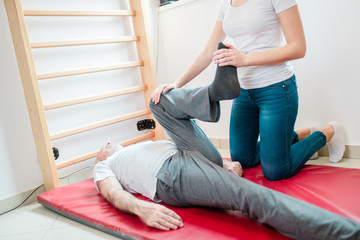 Senior man exercises in center for chiropractic.