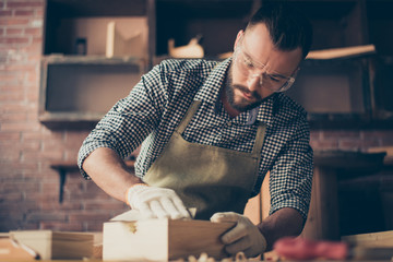 Handsome gifted hardworking confident concentrated bearded handyman clothed in checkered shirt apron gloves and safety glasses is sanding a little wooden casket with emery paper, working in a garage