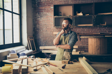 Confident concentrated pensive minded thoughtful serious bearded woodworker wearing checkered shirt and apron is thinking over brand new project, standing near desktop with instruments