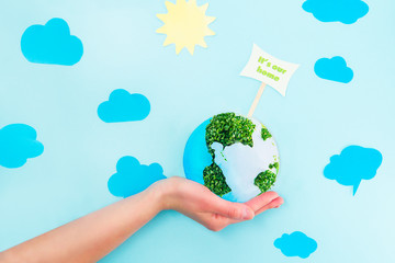 Female Hands holding Earth paper and green sprouts collage model with It's our home pointer on blue background with paper sun and clouds. Earth in your hands, Saving planet concept.