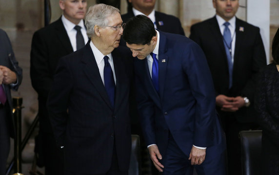 U.S. Senate Majority Leader McConnell whispers to Speaker of the House Ryan before ceremonies for the late evangelist Billy Graham lying in honor in the Rotunda of the U.S. Capitol in Washington,