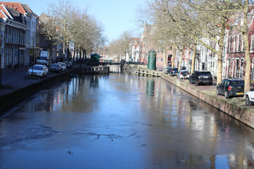 Canal in city of Gouda with thin layer of ice on it