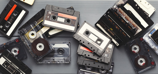 Heap of vintage audio cassettes at gray planks background