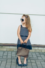 Funny little girl in black sunglasses and shoes oversized