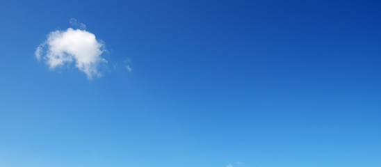 Panoramic photo with small cloud on bright blue sky background.