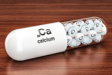 Capsule with Calcium Ca element on the wooden table. 3D rendering