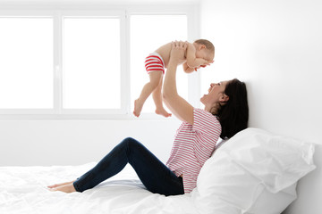 Smiling mother sitting on bed lifting baby in the air
